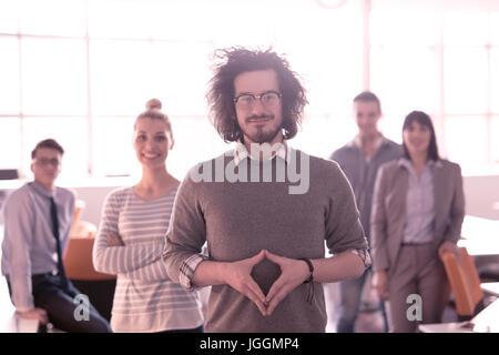 Porträt von lächelnden jungen Casuall Geschäftsmann mit Kollegen im Hintergrund im Büro - Stockfoto