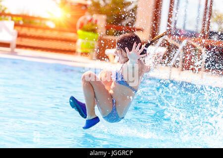 Aktive fröhliche Mädchen springen ins Wasser, Spaß im Pool auf das Beach-Resort, glückliche Sommerferien - Stockfoto