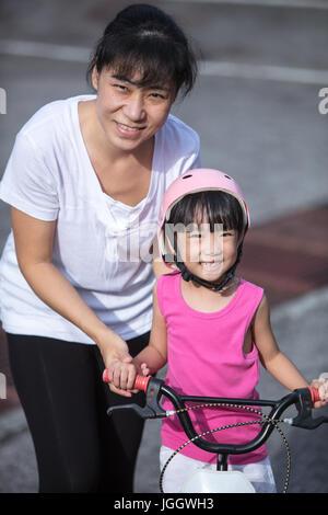 Asiatische chinesische kleinen Mädchen Reiten Fahrrad mit Mama guide auf Teerstraße im Freien. - Stockfoto
