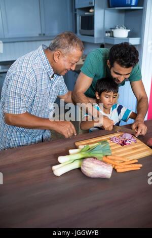 Erhöhte Ansicht des Mannes sah junge schneiden Zwiebel mit Vater in der Küche zu Hause - Stockfoto