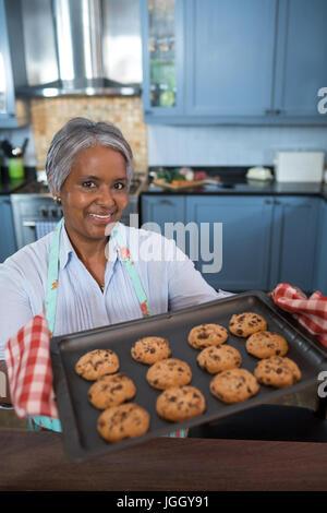 Hohen Winkel Porträt der Frau zeigt gebackene Kekse beim stehen in der Küche zu Hause - Stockfoto