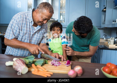 Vater Sohn stehend betrachten, indem Man schneiden Zwiebel in der Küche zu Hause - Stockfoto