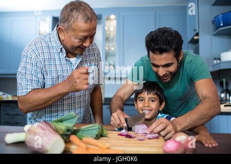 Man sah junge schneiden Zwiebel mit Vater in der Küche zu Hause - Stockfoto