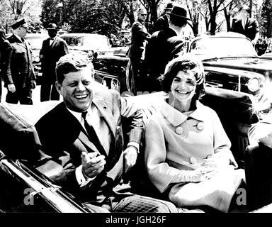 US-Präsident John f. Kennedy und Jacqueline Kennedy Lächeln beim Sitzen auf dem Rücksitz eines offenen Autos, John - Stockfoto