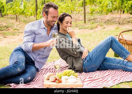Lächelnd jungen Mann mit Frau, Wein und entspannen Sie im Rasen - Stockfoto