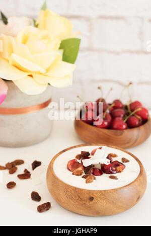 Haferflocken mit Joghurt und Obst. Kirschen, Rosinen und Kokos-Chips. Übernachtung Frühstück. Gesunde Ernährung - Stockfoto