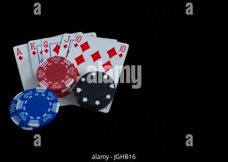 Erhöhte Ansicht der Karten und Chips auf schwarzem Hintergrund - Stockfoto