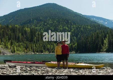 Voller Länge paar stehen am Seeufer gegen Berge - Stockfoto