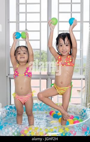 Gerne asiatische chinesische kleinen Schwestern spielen in den aufblasbaren Pool im Inneren des Hauses. - Stockfoto