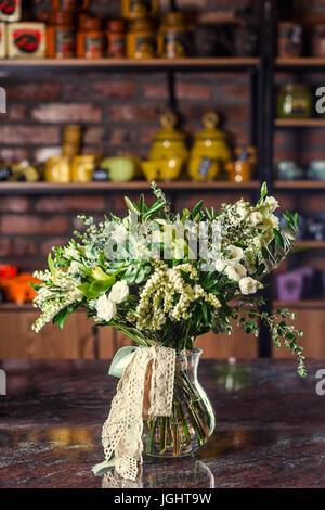 Noch immer leben von Blumen in einer Vase in der Küche mit vielen Dias und Vasen. Vase mit Rosen, Kaktus, Glocken