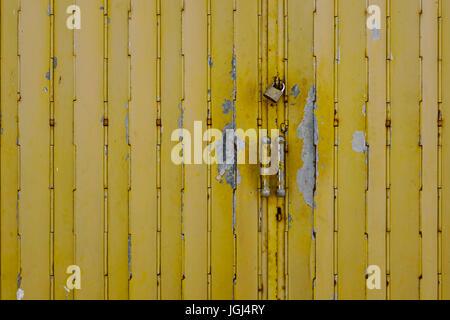 Gelbe alte Stahltür mit Schleuse am antiken Stadt. Hautnah. - Stockfoto