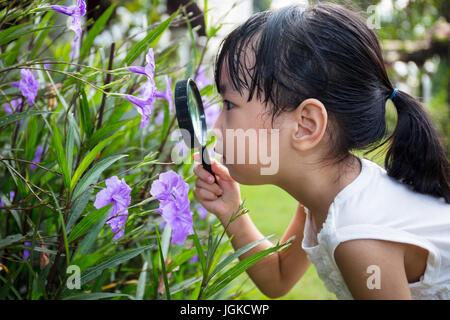 Asiatische chinesische Mädchen betrachten Blume durch ein Vergrößerungsglas im Garten