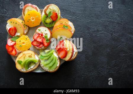 Frucht-Dessert-Sandwiches mit Ricotta-Käse. Gesundes Frühstück Toast mit Sahne-Käse, frisches Bio-Obst und Beeren, - Stockfoto