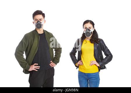 junge asiatische Mann und Frau trägt gas Maske starrte auf Kamera mit Armen gestemmt, isoliert auf weißem Hintergrund. - Stockfoto