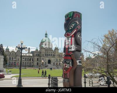 Eine erste Nationen Totempfahl Kwakiutl tragen Pole gegenüber der British Columbia Parlamentsgebäude Victoria Kanada - Stockfoto
