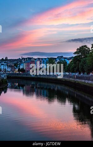 Sonnenuntergang und bunt bemalten Gebäude spiegelt sich in einem Fluss in Cork, Irland. - Stockfoto