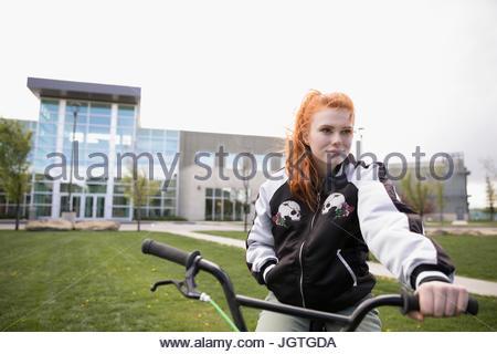 Porträt-weibliche College-Student mit roten Haaren Reiten Fahrrad auf Rasen auf College-campus - Stockfoto