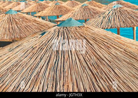 Strand-Sonnenschirme gemacht Stroh stehen hintereinander im hellen Sonnenlicht - Stockfoto