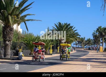Touristen auf 4-Rad Fahrrad auf cycleway, Strand Promenade an der Playa Matagorda Puerto del Carmen, Lanzarote, - Stockfoto