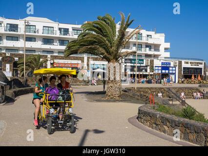 Touristen auf 4-Rad Fahrrad an der Promenade der Playa de las Cucharas, Costa Teguise, Lanzarote, Kanarische Inseln, - Stockfoto
