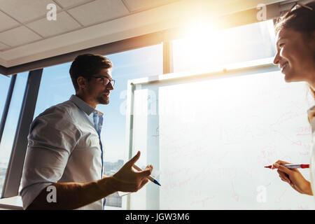 Bürokollegen diskutieren Geschäftsideen im Sitzungssaal. Mann und Frau Schreiben von Notizen am Whiteboard im Büro - Stockfoto
