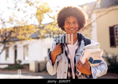 College-männliche Studenten tragen viele Bücher in College-Campus. Hübscher junger Mann mit Rucksack auf Straße. - Stockfoto