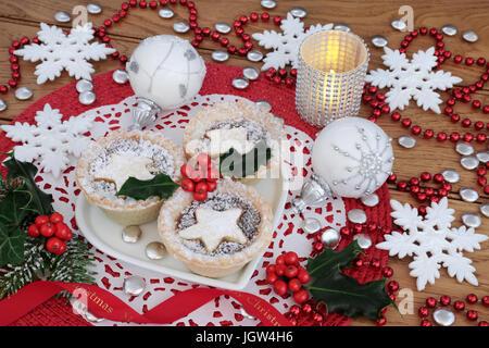 Mince Pies mit Holly auf einem Teller in Herzform mit Schneeflocke Christbaumkugel Dekorationen, Kerze und Perlen - Stockfoto