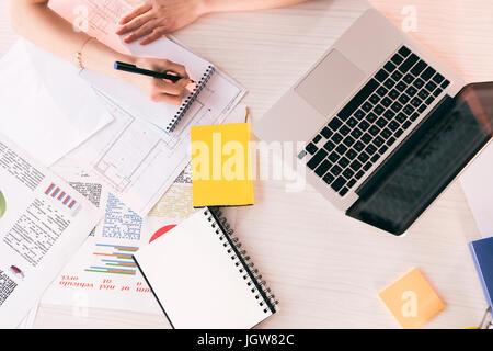 Schuss der Geschäftsfrau schreiben mit Stift am Arbeitsplatz auf Tischplatte mit Laptop zugeschnitten