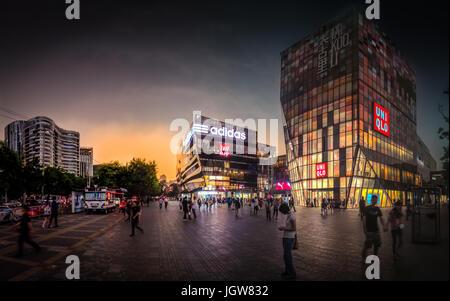 Einkaufen Vorplatz Uniqlo Gebäude voller Menschen in Sanlitun Peking bei Sonnenuntergang nach einem Gewitter - Stockfoto
