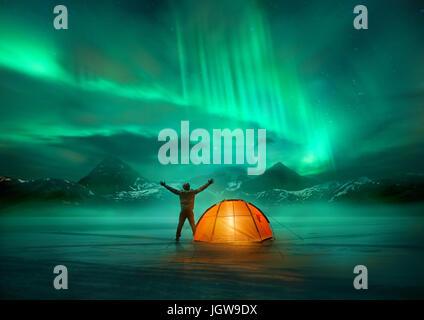 Ein Mann, camping in wilden nördlichen Berge mit einer beleuchteten Zelt eine spektakuläre grüne Nordlicht-Aurora - Stockfoto
