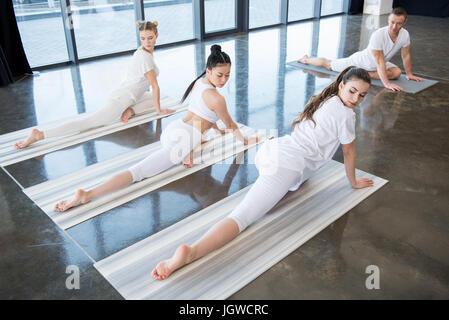 multiethnische Mädchen halb-Taube Yoga machen stellen mit Skilehrer im Haus - Stockfoto