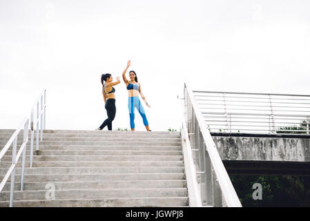 Zwei junge Frauen an Spitze der Treppe, feiert Training, South Point Park, Miami Beach, Florida, USA - Stockfoto