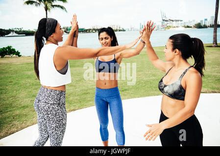 Drei junge Frauen im Freien tragen sportliche Kleidung, so dass hohe Fives, South Point Park, Miami Beach, Florida, - Stockfoto