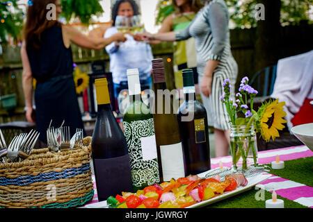 Gruppe von Frauen bei der Gartenparty, Weingläser halten, so dass Toast, Wein-Flaschen auf den Tisch im Vordergrund - Stockfoto