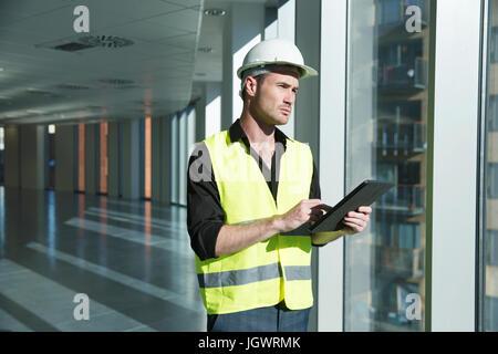 Mann, der hart trägt Hut und Hallo Weste Vis, Blick auf digital-Tablette - Stockfoto