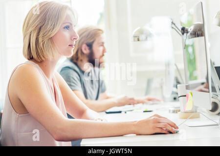 Männliche und weibliche Designer mit dem Desktop-Computer im Kreativstudio - Stockfoto