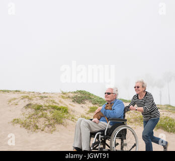Ältere Frau schob Mann im Rollstuhl auf Dünen, Playa del Ray, Kalifornien, USA - Stockfoto
