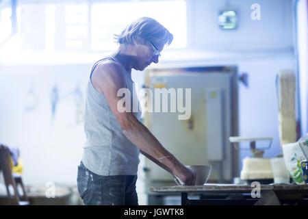 Ältere Frau in Töpferwerkstatt auf der Töpferscheibe, mache Becher - Stockfoto