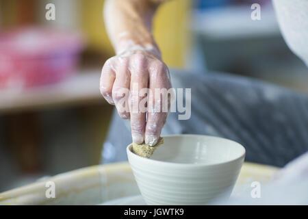 Ältere Frau in Töpferwerkstatt, mache Becher, close-up - Stockfoto