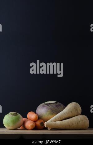 Stillleben-Anordnung von Wurzelgemüse (Rüben, Karotten, Schwede und Pastinaken) auf einem Holz beplankt Tisch mit - Stockfoto