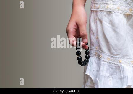 Schwarze Perlen Armband in Mädchen Hand. Kann als modische Accessoires verwendet werden, auch als Gebet Perlen, die für die Zählung von Gebeten oder üben Achtsamkeit meditatio
