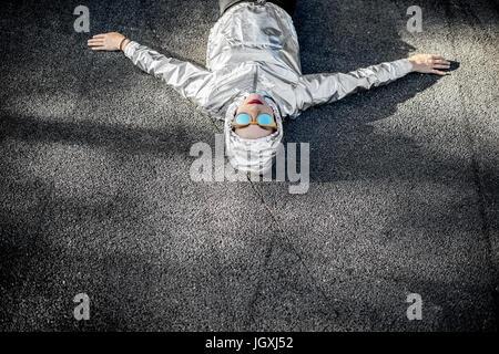 Lifestyle-Porträt einer modernen Frau in Silber-Jacke mit Kapuze und Sonnenbrillen liegen im Freien auf der Asphaltstraße - Stockfoto