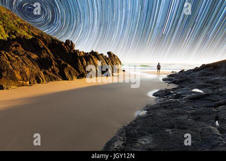 Ein Mann steht auf einem schönen, abgelegenen Strand in Australien unter eine faszinierende Sternspur - Stockfoto