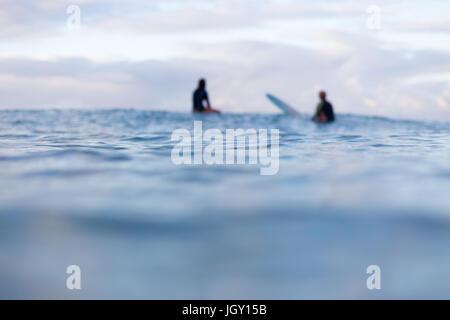Zwei von Fokus Surfer sitzen in der Ferne auf ihren Surfbrettern, während sie darauf warten, für eine Welle am Horizont - Stockfoto