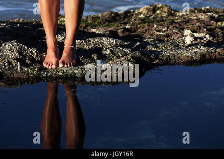 Einer jungen Frau den durchtrainierten Beine und nackte Füße spiegeln sich in einen ruhigen Felsenpool wie sie eine - Stockfoto