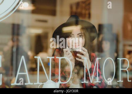 Porträt der jungen Frau im Café sitzen, Blick durch Fenster - Stockfoto