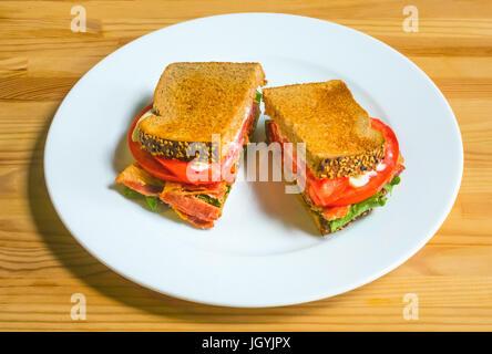 Ein BLT auf einem weißen Teller mit Speck, Salat, Tomate, und Mayonnaise auf geröstetem Brot, einer klassischen - Stockfoto