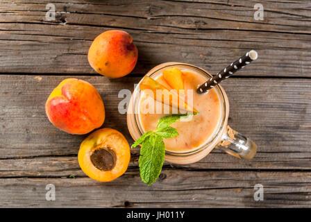 Hausgemachte Bio Smoothie aus Joghurt und Aprikosen. In Mason Jar, auf einem urigen alten Holztisch mit Aprikosen - Stockfoto