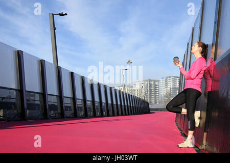 Junge Frau (Alter 30) hat eine Kaffeepause aus, die auf einem hellen rosa Cycleway Straße in Auckland, Neuseeland. - Stockfoto
