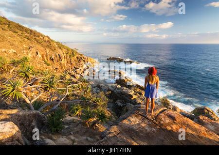 Eine junge Frau bewundert Küsten Blick über das Meer bei Sonnenaufgang in der Nähe von Coffs Harbour, Australien. - Stockfoto